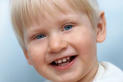 A young boy smiling and showing his teeth.